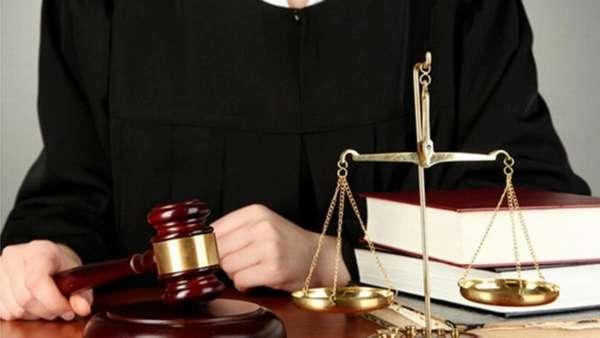 судья, судейский молоток и весы, стопка книг на столе