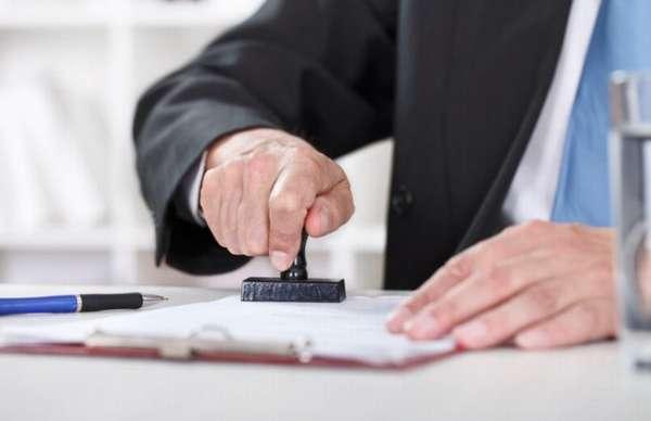 юрист ставит печать на документах на столе