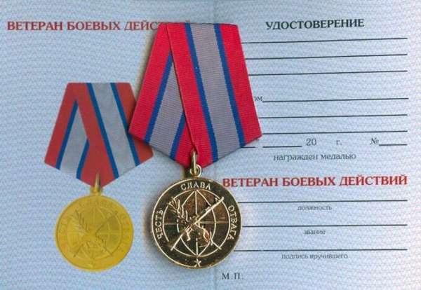открытое удостоверение ветерана боевых действий и медаль за отвагу