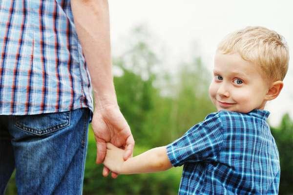 маленький мальчик держит отца за руку