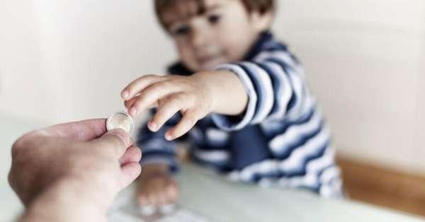 малнький ребенок берет монетку с рук