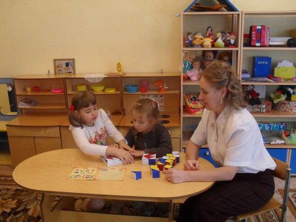 дети за столом играют в кубики с воспитателем в детском саду