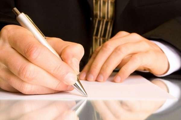 ручка в руках и бумага на столе