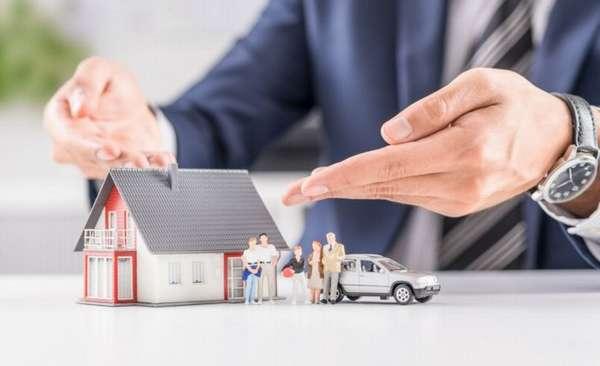 человек показывает руками на декоративный домик, семью и машину