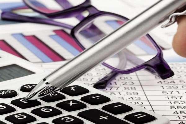 ручка, калькулятор, очки и бумаги на столе