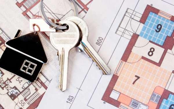 связка ключей с брелком в виде домика на строительном плане дома