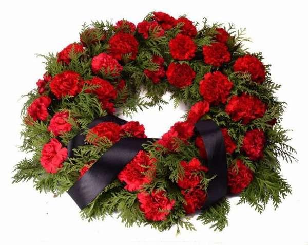 похоронный венок из красных цветов с черной ленточкой