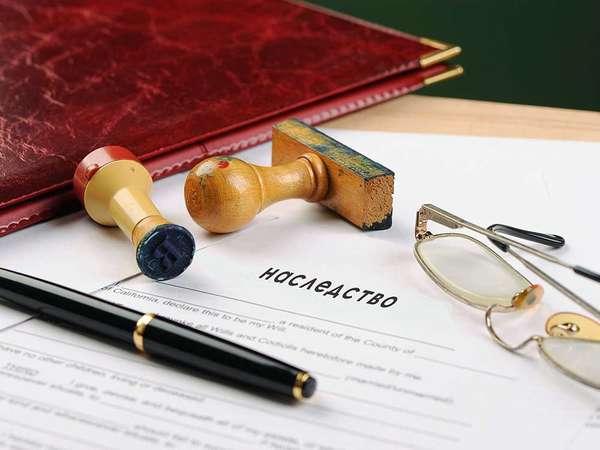 папка с документом о наследстве, очки, ручка, печати и паспорт на столе