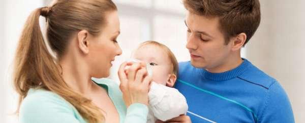 родители кормят маленького ребенка с бутылочки
