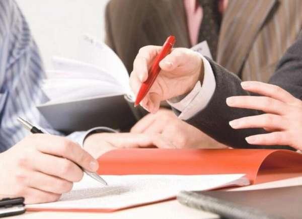 красная папка с документами на столе, ручки в руках