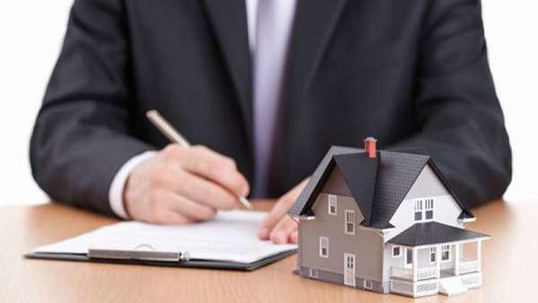 мужчина заполняет документы ручкой, маленький домик на столе