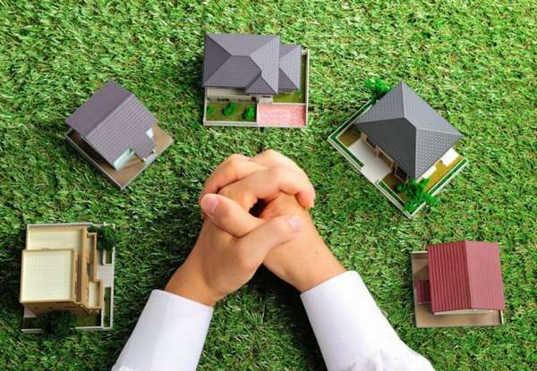 пять декоративных домиков на траве и сложенные руки