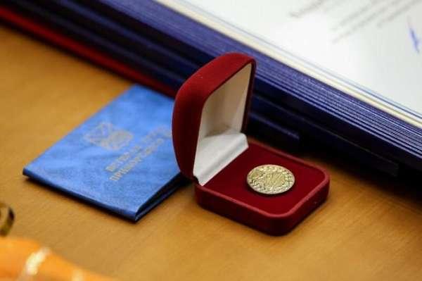 синее удостоверение ветерана труда и золотая медаль в красной коробочке на столе