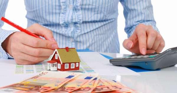 деньги, декоративный домик, калькулятор и документы на столе