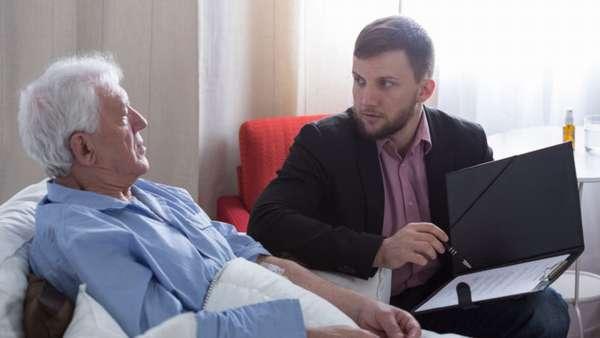 пожтлой мужчина и юрист обсуждают документы в папке