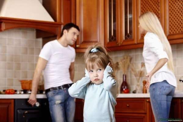 маленькая девочка закрывает уши руками, сорра родителей на фоне