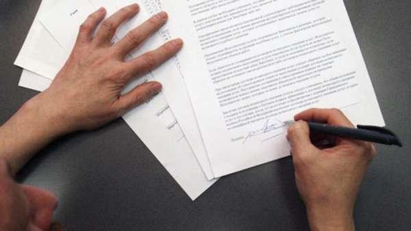 подписывание документа ручкой на столе