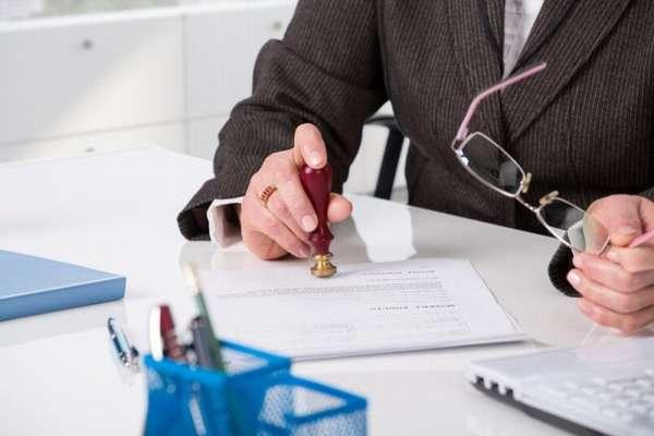 юрист ставит печать на документе и держит в руке очки