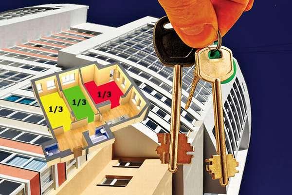 ключи в руках и многоэтажный дом на фоне