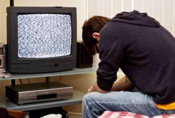 человек сидит перед нерабочим телевизором