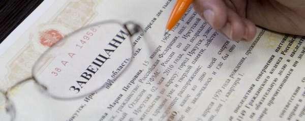 завещание, очки и оранжевая ручка в руке