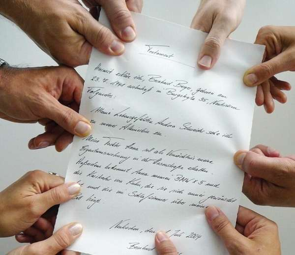 группа рук держат написанное от руки завещание