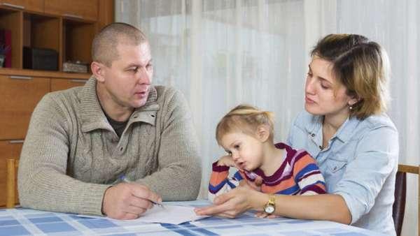 родители с ребенком и документ на столе
