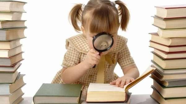 стопки книг на столе, маленькая девочка читает книгу черех лупу
