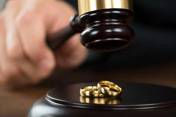 судейский молоток и обручальные кольца на деревянном блине