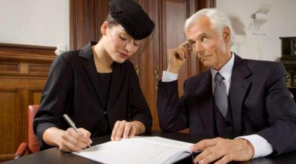 женщина в черной одежде заполняет документы и рядом сидит пожилой мужчина